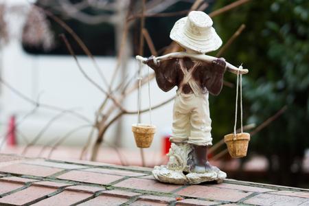 carrying water children's sculpture. garden trinket Foto de archivo - 99048057