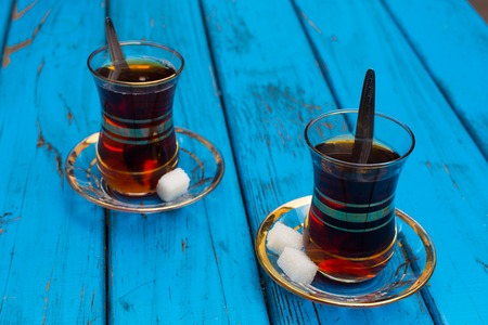 Black Turkish tea. Turkish national drink. well-brewed tea; It is called rabbit blood. isolated blue background. side view. Free space for your text Stock Photo
