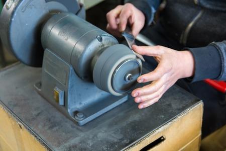 knife sharpening machine and master. Grinding machine. grinding knife using abrasive stone Imagens