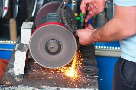 Messerschleifmaschine und Meister. Schleifmaschine. Schleifmesser mit Schleifstein