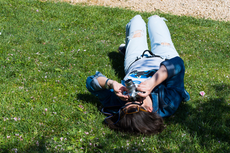 beautiful woman photo shoot.beautiful woman lying in the grass is taking pictures Zdjęcie Seryjne