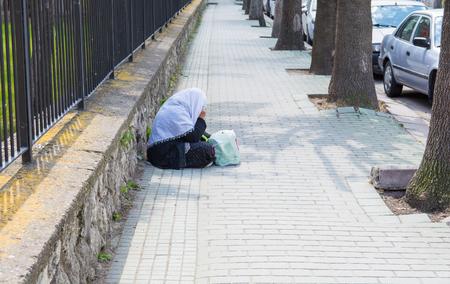 beggar sitting on the street. female beggar. Wants money for Ramadan Banco de Imagens