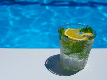 enjoying fresh lemon and mint mojito cocktail by the pool