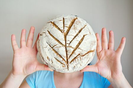 woman poses with bread at the camera. bread smoothie women. Homemade natural organic bread. siyez flour. basic vegan food