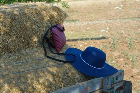 on top of straws, womans hat and bag