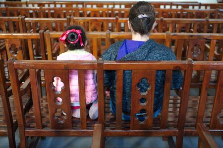 mother and daughter waiting in assembly hall.