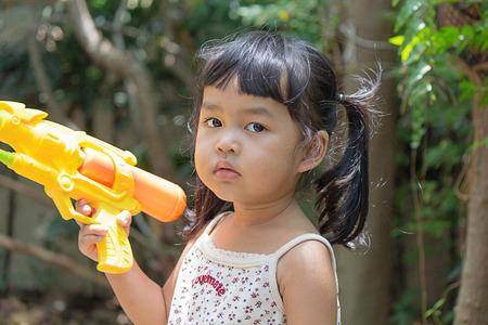 water gun: Asian kid playing water gun Stock Photo