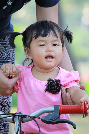 tried: Asian baby girl tried to ride bicycle at Suanluang Rama 9 Public National Park Bangkok, Thailand