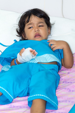 sickbed: Illness little asian kids crying, asleep on a sickbed in hospital, saline intravenous IV on hand