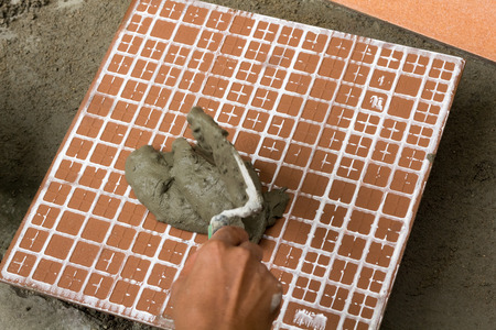 tile adhesive: a tiler at work. bonding of floor tile with tile adhesive and filler. Stock Photo