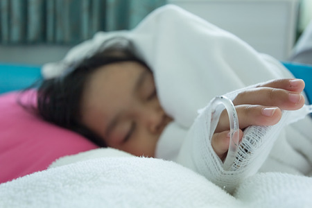 bebe enfermo: Illness asian kids asleep on a sickbed in hospital, saline intravenous IV on hand