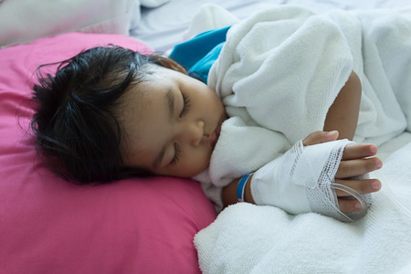 sickbed: Illness asian kids asleep on a sickbed in hospital, saline intravenous IV on hand