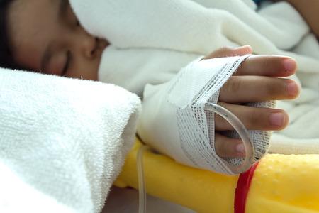 sickbed: Illness asian kids asleep on a sickbed in hospital, saline intravenous IV on hand