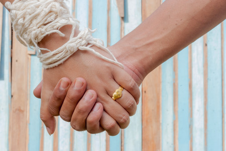 hold hands: bride and groom hold ones hands with color wooden background Stock Photo
