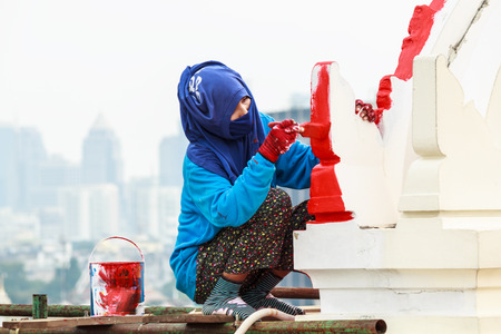 Woman painter with blue mask painting red color at high building.