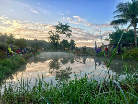 FANG,CHIANG MAI/THAILAND - DECEMBER 22,2018: Fishermen catch fish at the lake in the morning with beautiful sky