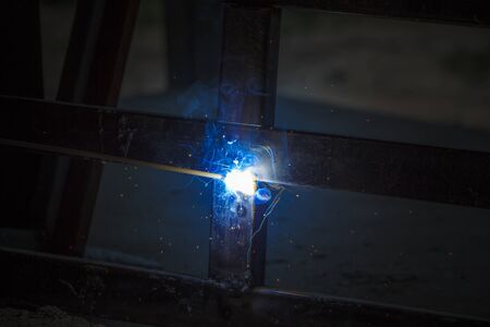 Welding Process with black block metal and bright sparks in steel