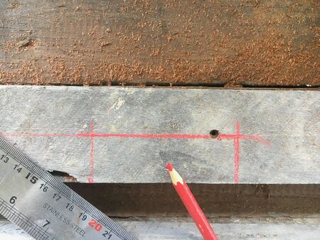 close up marking measurements on the wooden plank
