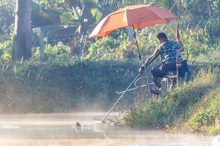 FANG, CHIANG MAI/THAILAND - DECEMBER 22, 2018: Fishermen catch fish at the lake in the morning with beautiful sky 報道画像
