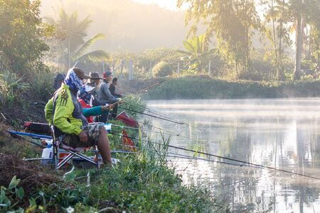 FANG,CHIANG MAI/THAILAND - DECEMBER 22,2018: Fishermen catch fish at the lake in the morning with beautiful sky 報道画像