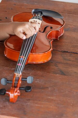 Hand of a kids with a violin shallow deep of field