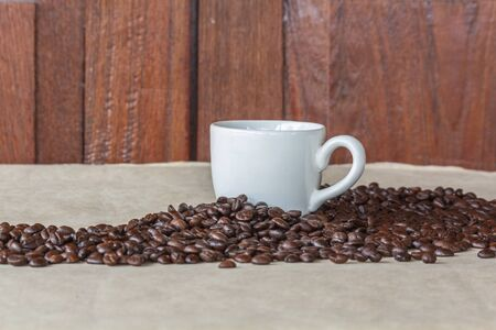 White cup of coffee and coffee grains surrounded 写真素材