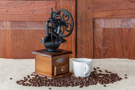 Manual coffee grinder with  black coffee beans 写真素材