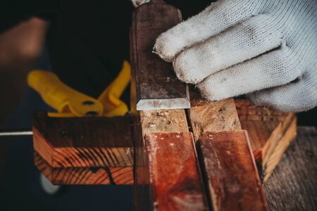 The hand of the asian carpenter taking the chisel to sharpen the wood plank