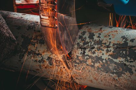 Close-up of Electric Grinder Cutting metal pipe with Bright Sparks tails 写真素材