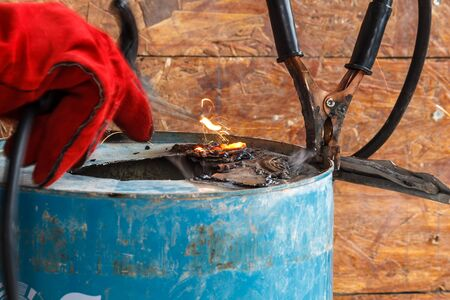 Worker with red glove to protect spark light with welding Process with blue tube metal and bright sparks in steel