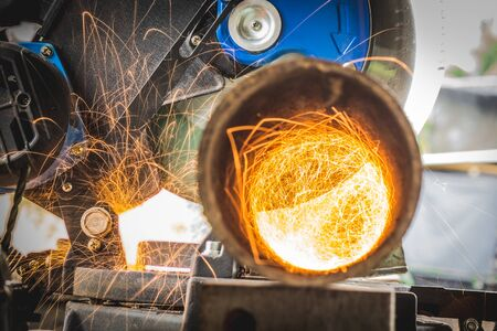 Close-up of Electric Grinder Cutting metal pipe with Bright Sparks