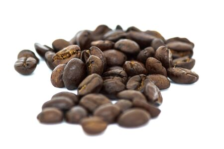 Closeup of roasted black coffee beans on white background
