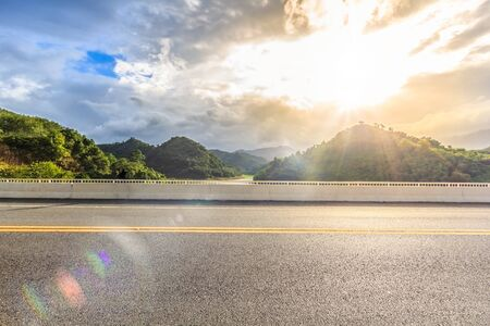Asphalt road side view with Green Lake , beautiful sky and lens flare in Betong, Yala, Thailand