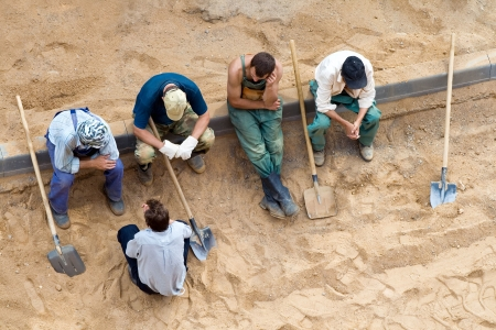 indolence: Sitting workers with shovels on the rest