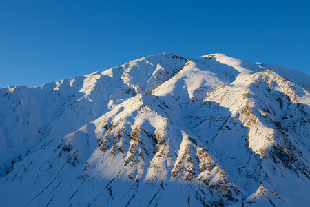 caresses: Beautiful Caucasian mountains at sunset, the sun caresses the teeth of the mountains. Winter time.