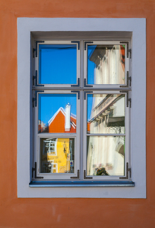 Reflection of bright and colorful houses in window. Old town of Tallinn. Reklamní fotografie