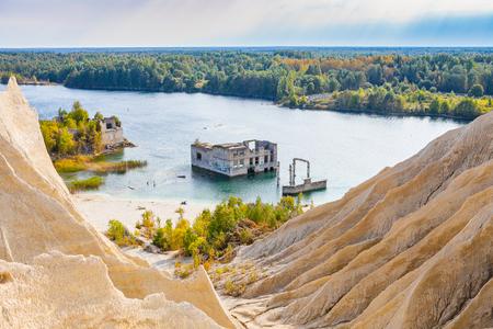 Zandheuvels van steengroeve met een vijver en een verlaten gevangenis in Rummu, Estland