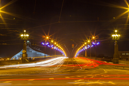 Riga stone bridge in the night. Illuminated road and building of National library.