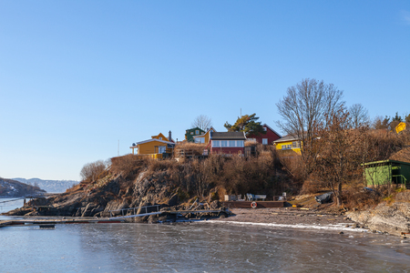 summerhouse: Color wooden cabins on the island with frozen sea and rocks at the foreground. Scandinavian style. Sunny winter day