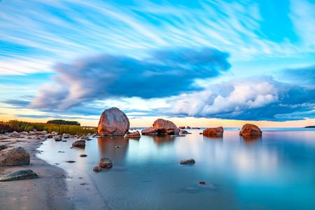 明るい色の石の海岸沿いで海の夕日 写真素材