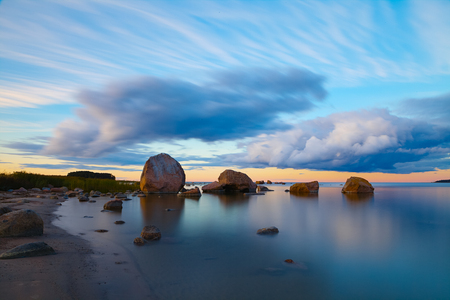 Tranquil view of sunset with stones along a shore of the Baltic Sea in Estonia.