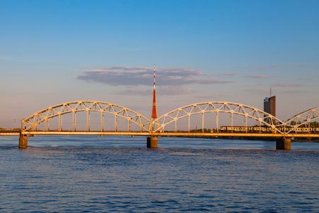 Train is running by the bridge over Daugava. TV tower and sunset time. Riga, Latvia