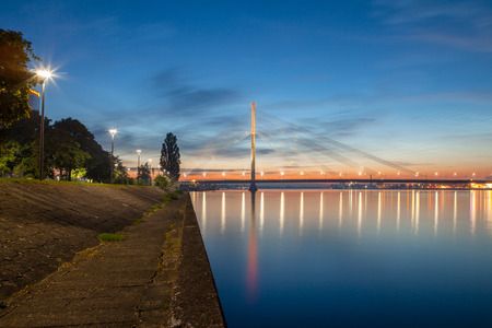 Deep sunset panoramic scene over Daugava river in Riga, Latvia. New business buildings and cable-stayed bridge