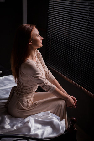 jalousie: Beautiful young woman in dark interior, sitting on bed, watching at window covered by jalousie. Red haired girl wore in long classic dress.