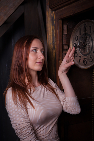 Portrait of young woman in low key with vintage clock at the background. Studio shot.