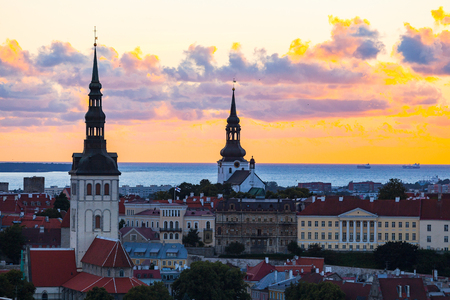 Orange sunset over old town of Tallinn, Estonia. Cathedrals towers and medieval buildings aerial view. Stock Photo