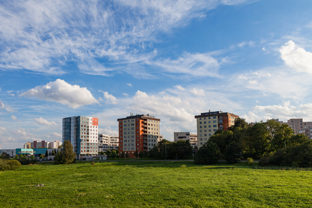 New modern blocks of flats in green area with blue sky at summer day. Northern friendly style.
