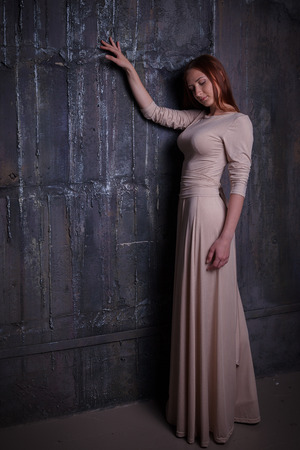 expensive: Beautiful elegant young woman wore in long dress standing in front of dark vintage wall.