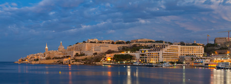 Summer amazing night view of Valetta profile over sea. Long exposure. Illuminated architecture. Wide panoramic view.