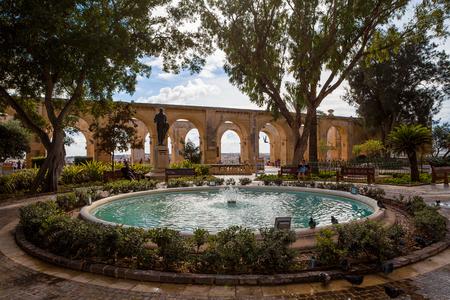 Sparkling Brunnen unter ruhigen Bäumen und Kalkstein Bögen im Hintergrund, Upper Barrakka Gardens Park, Hauptstadt von Malta, Valletta. Standard-Bild - 85106063